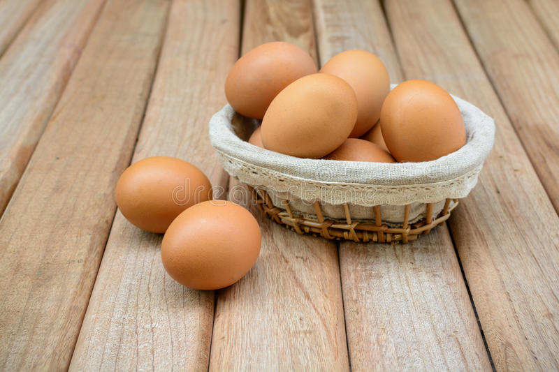 Eggs in basket on wooden background royalty free stock photos