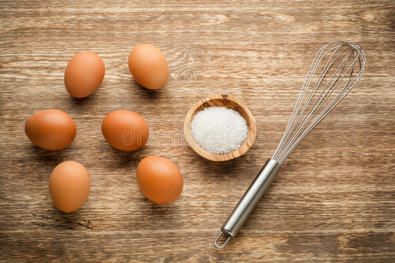 Eggs with beater and salt on wooden table stock images
