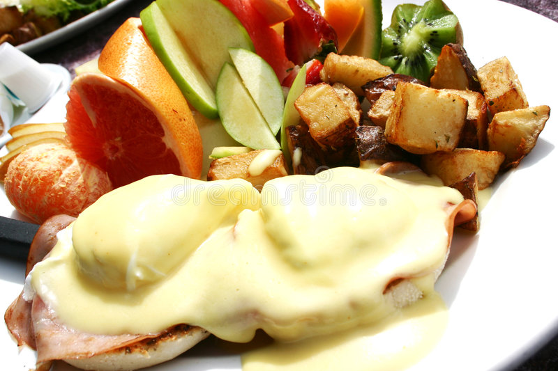 Eggs benedict. With lot of fresh fruits