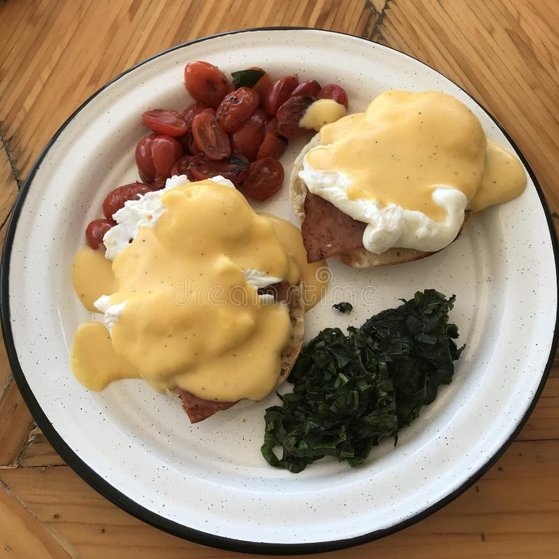 A plate of Eggs Benedict with fried cherry tomatoes and greens on a white plate stock photos