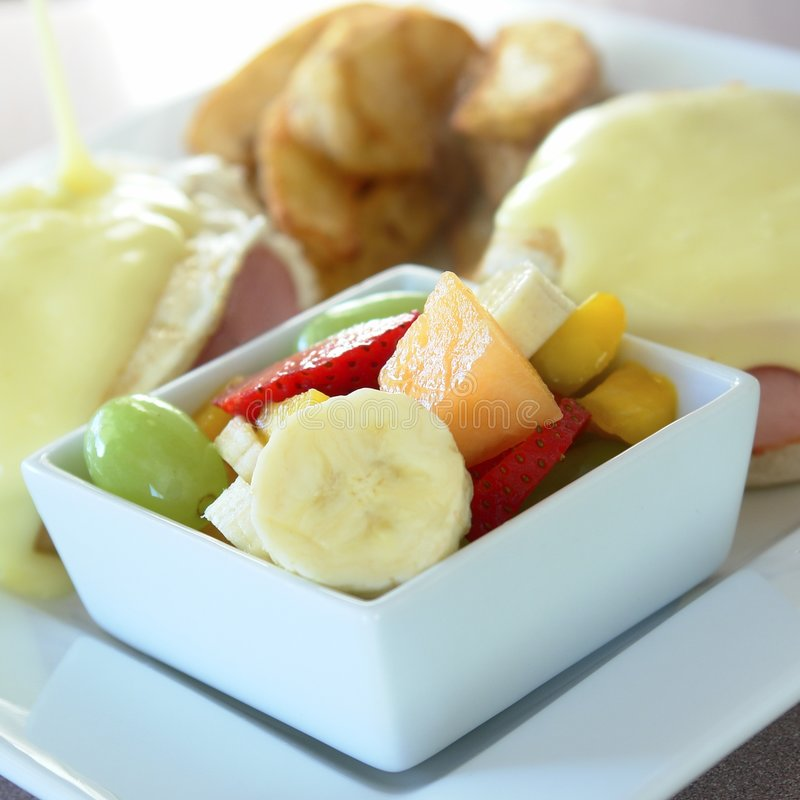 Eggs Benedict Breakfast Fruit. Breakfast plate with eggs benedict, fried potatoes and fresh fruit royalty free stock image