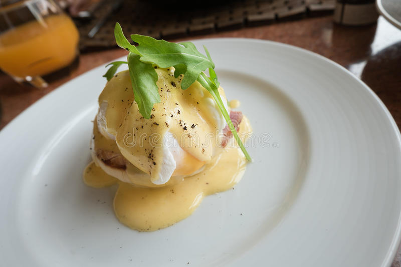 Eggs Benedict, an English muffin topped with ham or bacon, a poached egg and hollandaise sauce on a white plate. stock photography