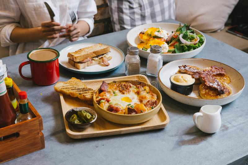 Eggs Benedict, Crispy Bacon stuffed French toast, Cheesy Potato with Crispy Bacon and Pancakes with Maple Syrup, Bacon. stock photo