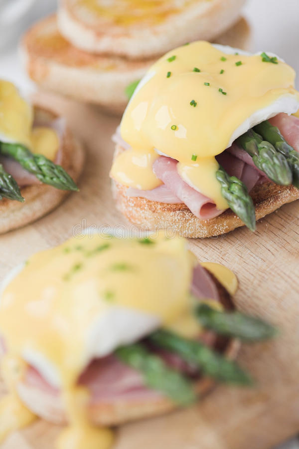 Eggs Benedict with ham & asparagus. Shallow dof stock images