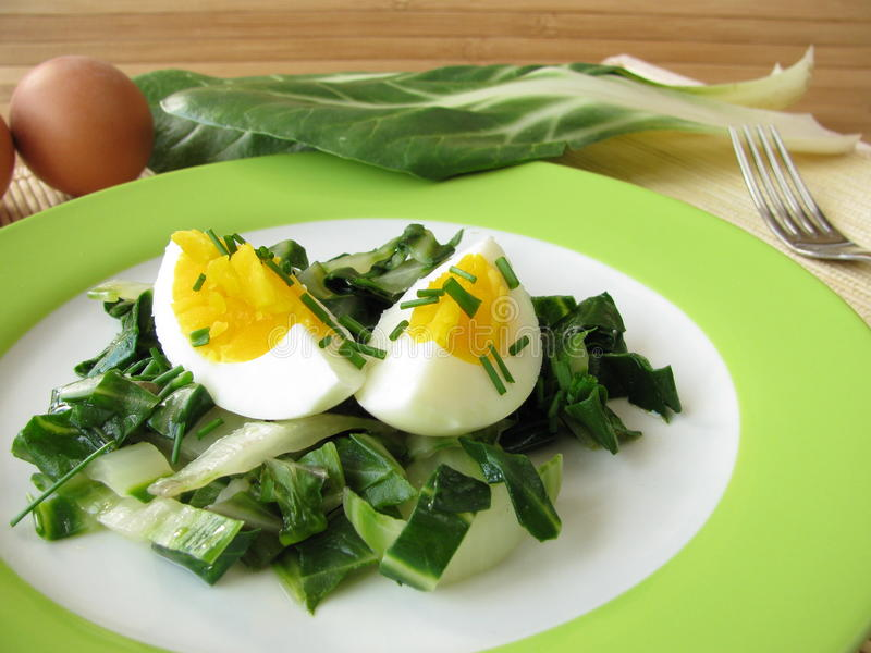 Eggs on chard vegetables royalty free stock photography