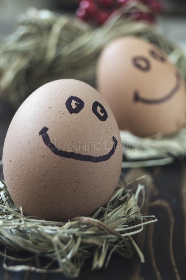 Eggs with drawn funny faces on straw. Close up of eggs with drawn funny faces on straw stock photo
