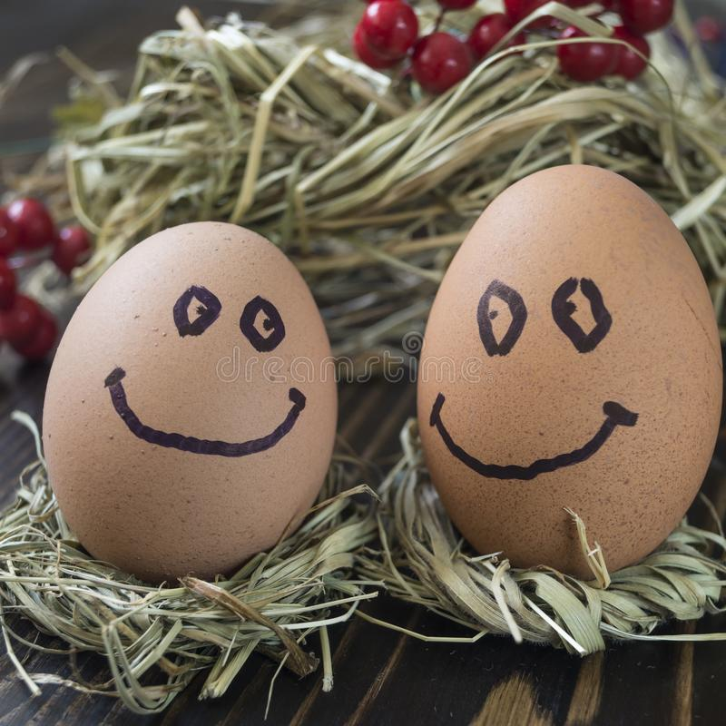 Eggs with drawn funny faces on straw. Close up of eggs with drawn funny faces on straw stock photos