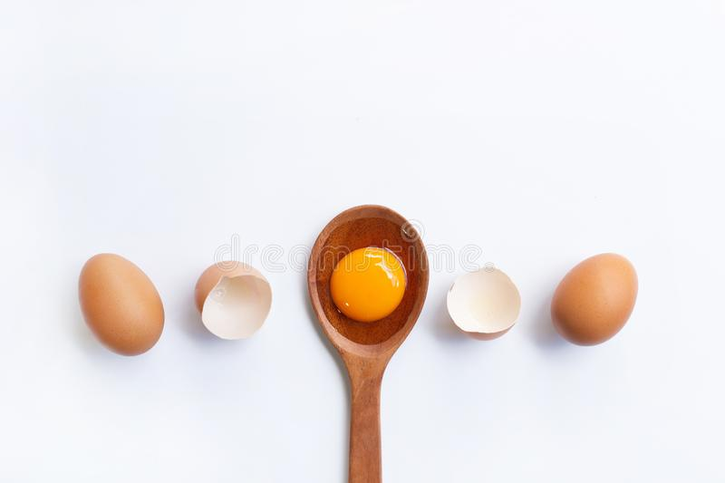Eggs, egg yolk on wooden spoon isolated. On white background stock photos