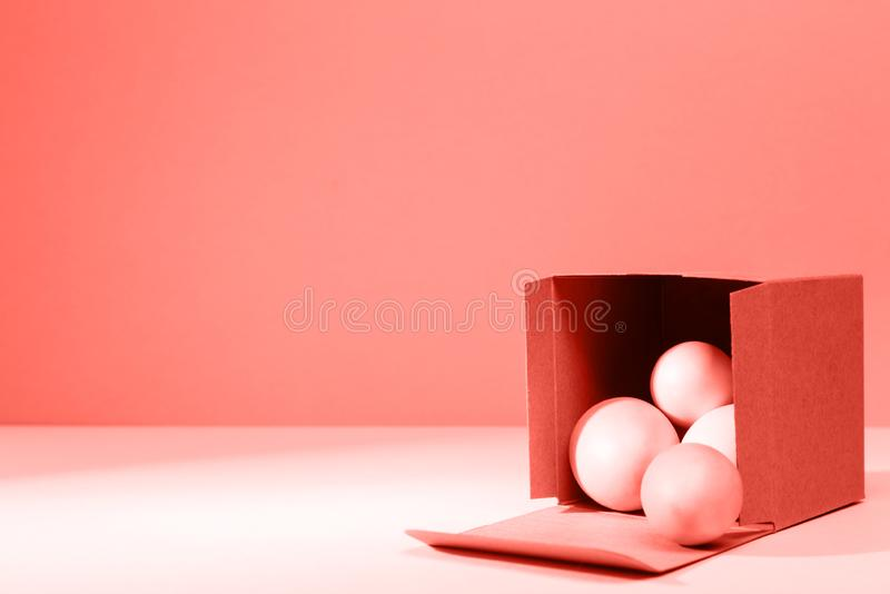 Eggs falling out of the craft cardboard box. Creative Easter concept. Modern solid background . Living coral theme - color of the. Eggs falling out of the craft stock images
