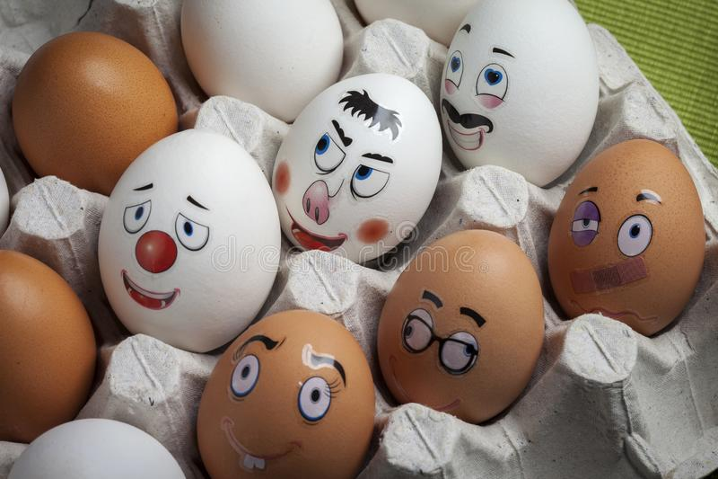 Funny eggs with different faces painted with different emotions. Eggs with funny faces painted in an egg holder. Creative egg decorating for Easter stock photos