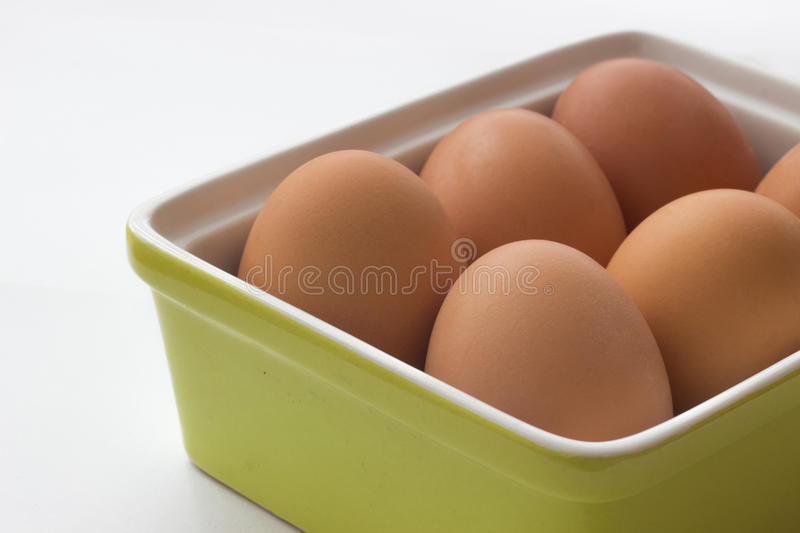 Eggs in green container. Brown eggs in green container stock photos