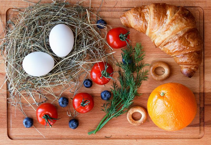 Morning meal with an orange, eggs and a croissant stock photos