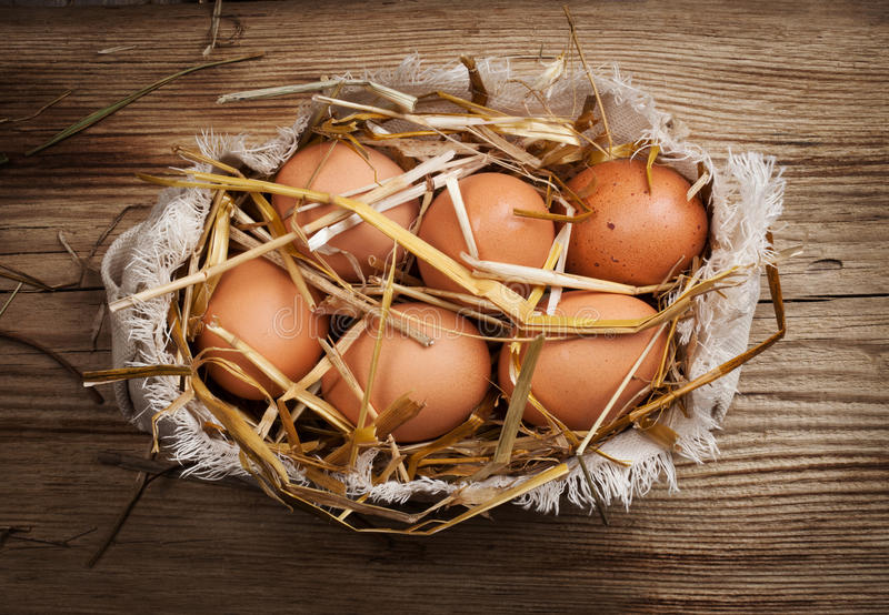 Eggs in hay. On wooden background stock photo