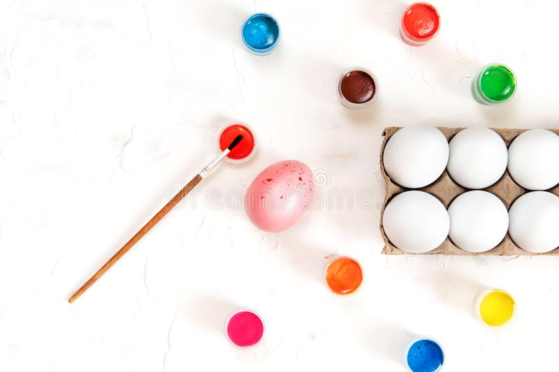 Eggs and paints on a white background. Coloring easter eggs royalty free stock images