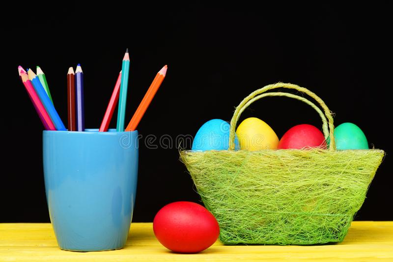 Eggs and pencils. Coloured crayons in blue mug and Easter decorations in green basket and red egg lying on yellow wooden stock photography