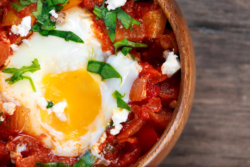Eggs poached in tomato sauce and red, yellow pepper, onion stock image