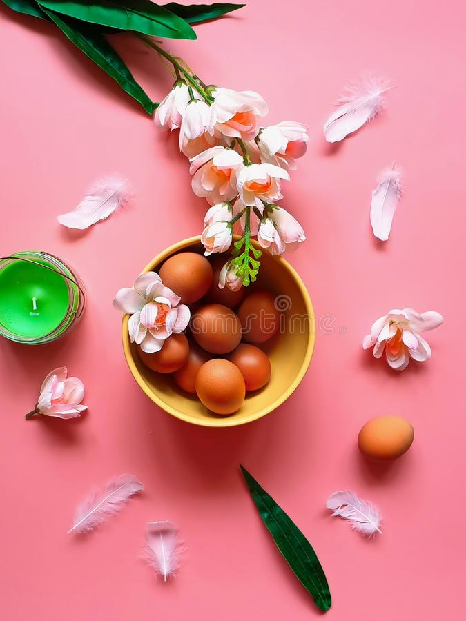 Eggs  Protein rich food vitamin Pink white apple flowers  green aroma  candle yellow plate on pink  Healthy  f. Happy Easter greetings card Holiday ,healthy Food stock photography
