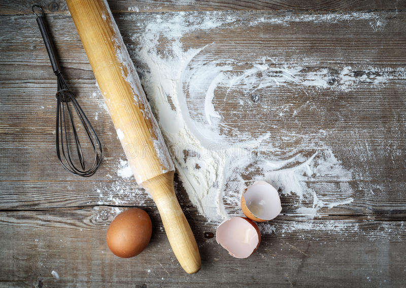 Eggs, rolling, whisk. Still life with eggs, rolling pin, flour and whisk on vintage wood table background. Top view stock photos