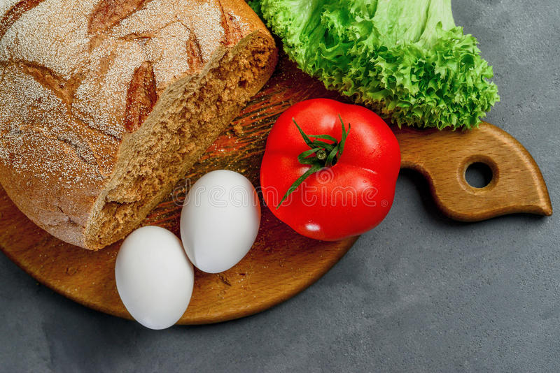 Eggs, tomato, lettuce leaves, bread. Wooden board with Ingredients for cooking. From above royalty free stock photos