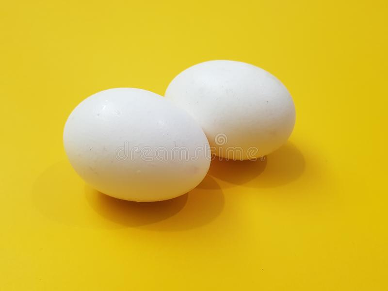 Eggs. Two small eggs on yellow background royalty free stock image