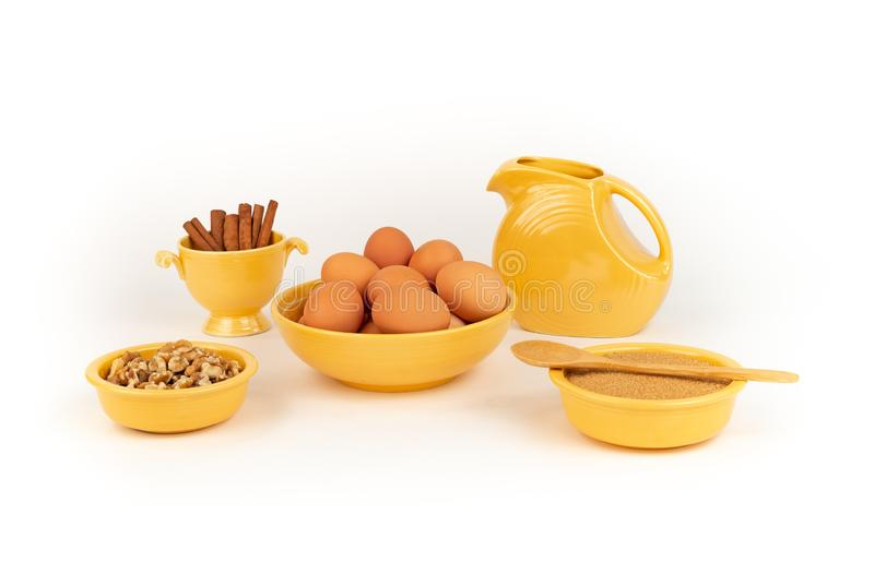 Eggs, Walnuts, Organic Sugar, Cinnamon, in Vintage Yellow Fiesta Ware bowls with Large Pitcher. stock images