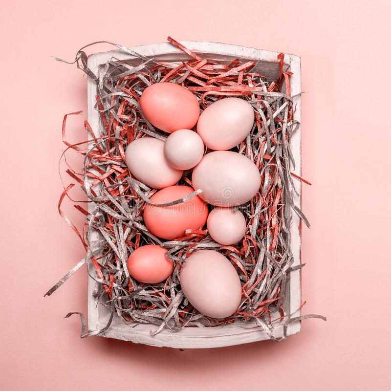 Eggs in a white tray. Creative Easter concept. Modern solid pink background. . Living coral theme - color of the year 2019. Eggs in a white tray. Creative Easter stock photo