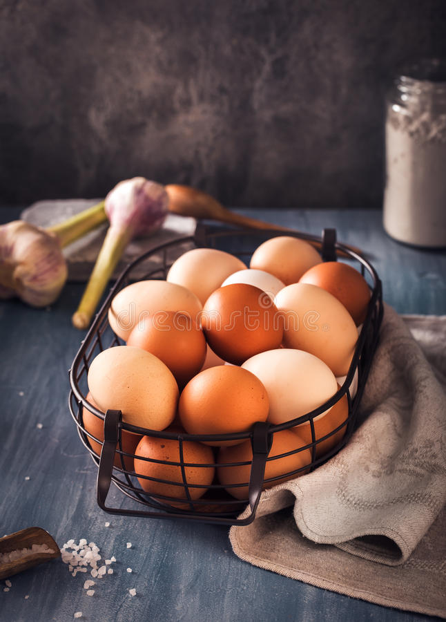 Eggs in wire basket on rustic table stock photos