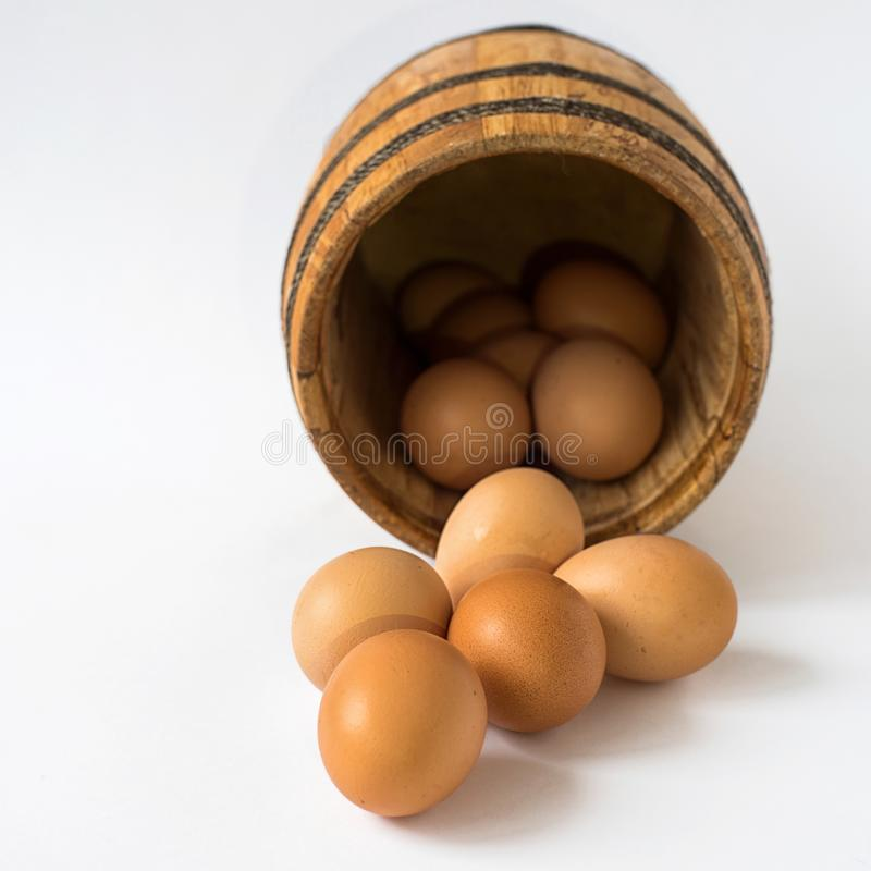 Eggs in wooden barrel on white background stock photo