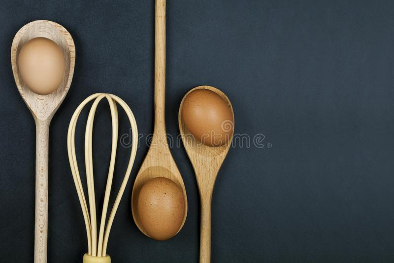 Eggs, wooden spoon and whisker. Kitchen utensil for cake, pastry or cookies on backboard background royalty free stock image