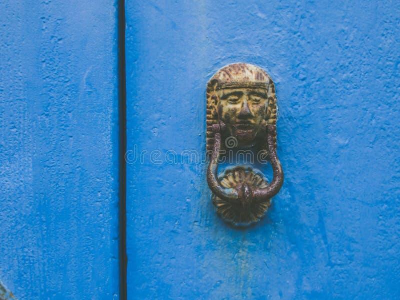 Egipskiego metalu drzwiowy knocker na starym błękitnym drzwi zdjęcia royalty free