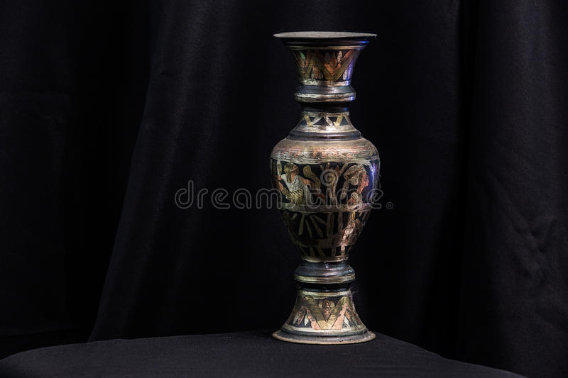 Egiptian metal vase. On black cloth background stock photography