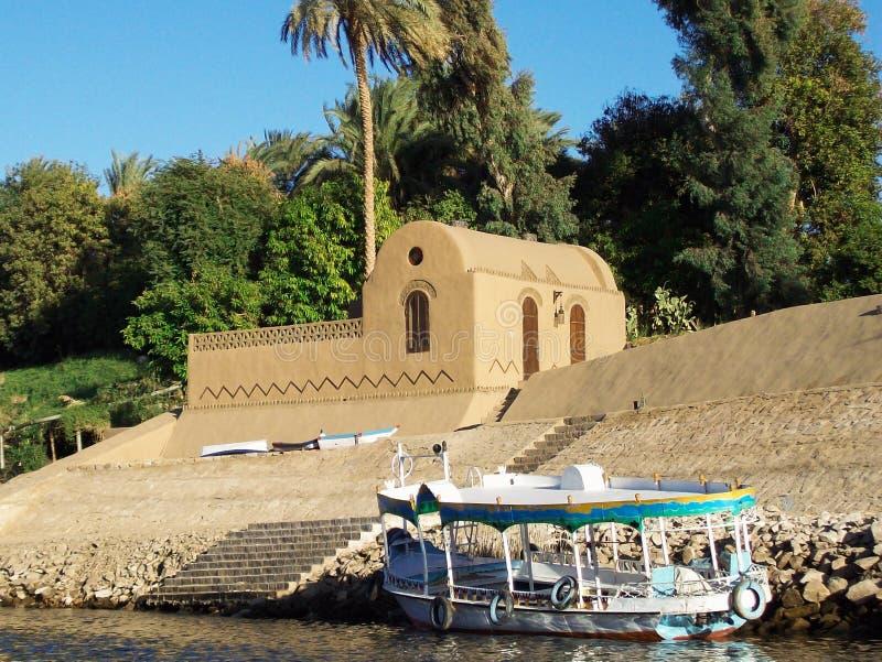 Egito, Nilo, casa egípcia no banco do rio, com o barco amarrado fotografia de stock royalty free