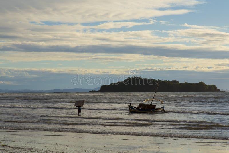 Żeglarz splata łódź na niskiego przypływu morzu w zmierzchu obrazy royalty free