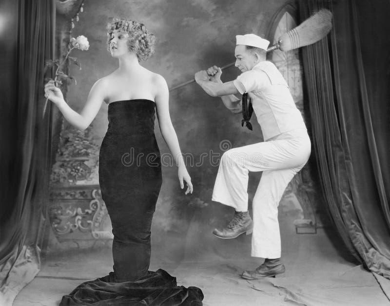 Żeglarz uderza eleganckiej kobiety z miotłą (Wszystkie persons przedstawiający no są długiego utrzymania i żadny nieruchomość ist obrazy royalty free