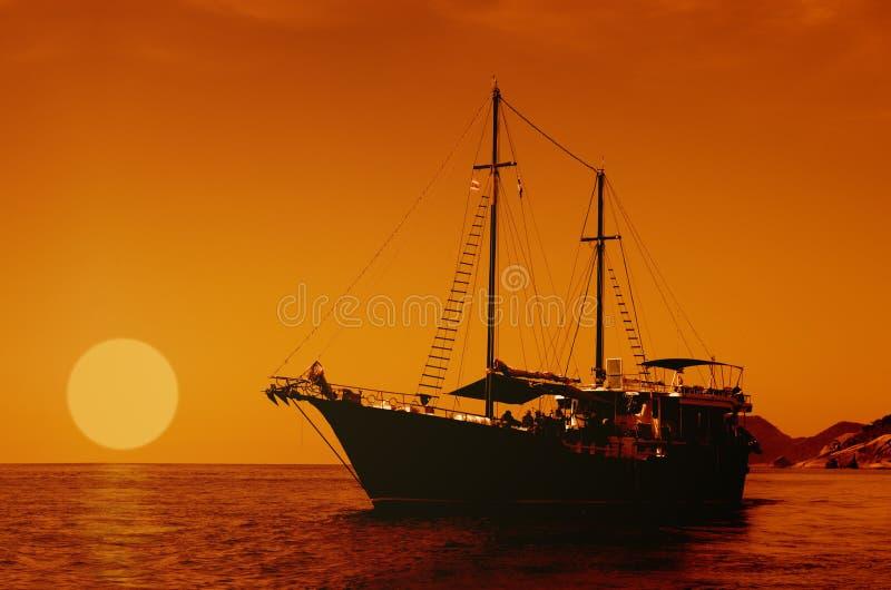 Żeglowanie statek na morzu przy zmierzch linią horyzontu zdjęcie stock