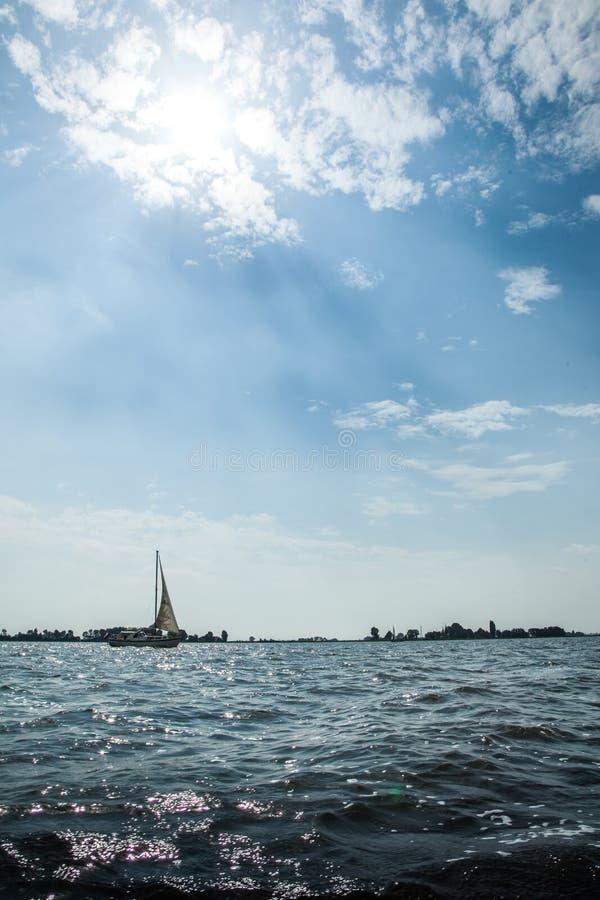 Żegluje statek na jeziorze z chmurami i słońcem z wyspą zdjęcia royalty free