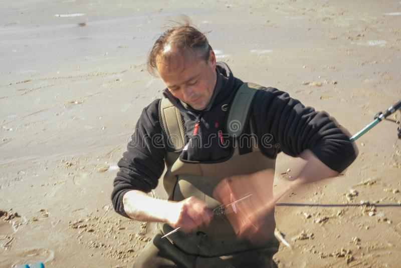 Egmond-aan-Zee, Netherlands - 2016-04-10: Fisherman rolling up the fishing line. Sea fishing competition along the Northsea shore royalty free stock image