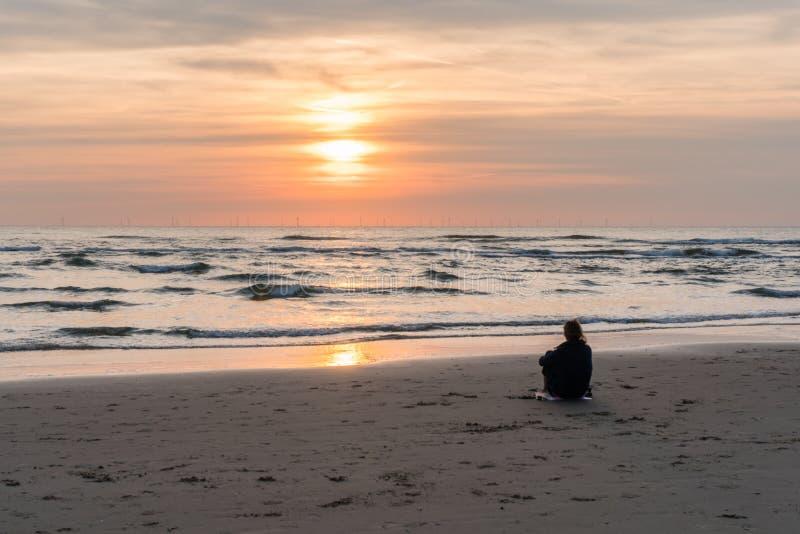 Egmond-aan-Zee, Netherlands, 09-24-2016: Girl at the seafront sunset stock photo