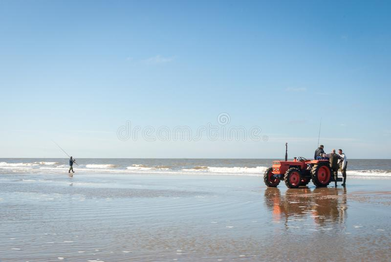Egmond-aan-Zee, Netherlands - 2016-04-10: Red tractor on the shore during the Sea fishing competition along the Northsea shore royalty free stock photo