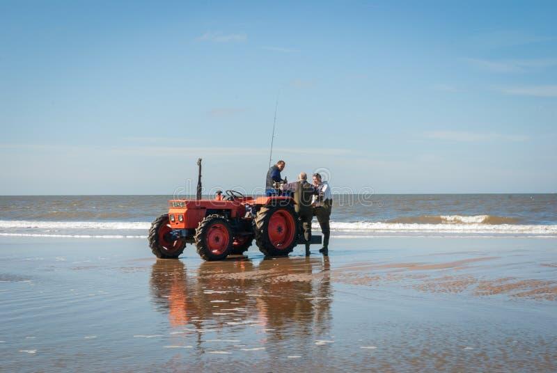 Egmond-aan-Zee, Países Baixos - 2016-04-10: 3 homens da organização com um trator vermelho na praia imagem de stock royalty free