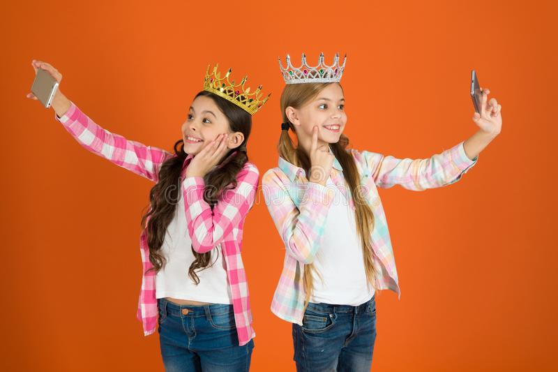 Egocentric princess. Kids wear golden crowns symbol princess. Warning signs of spoiled child. Avoid raising spoiled kids. Girls taking selfie photo smartphone royalty free stock image
