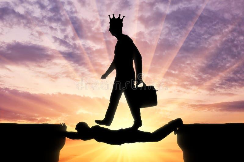 Egoistischer Mann mit einer Krone auf seinem Kopf geht ?ber einen Mann in Form einer Br?cke ?ber einem Abgrund stockfotografie