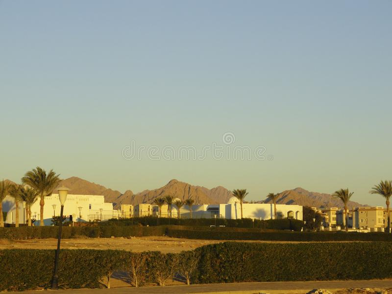 Egypt: buildings under construction in the desert among the sands in the rays of the rising sun. In the early morning royalty free stock photography
