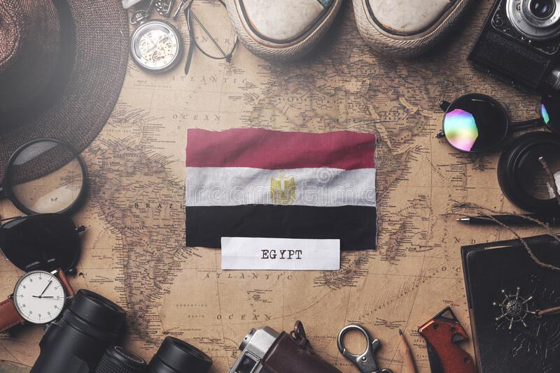 Egypt Flag Between Traveler`s Accessories on Old Vintage Map. Overhead Shot.  stock images
