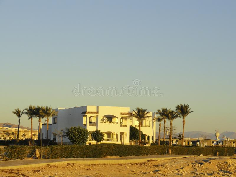 Egypt: Lonely standing building in the desert among the sands in the rays of the rising sun. In the early morning stock photography