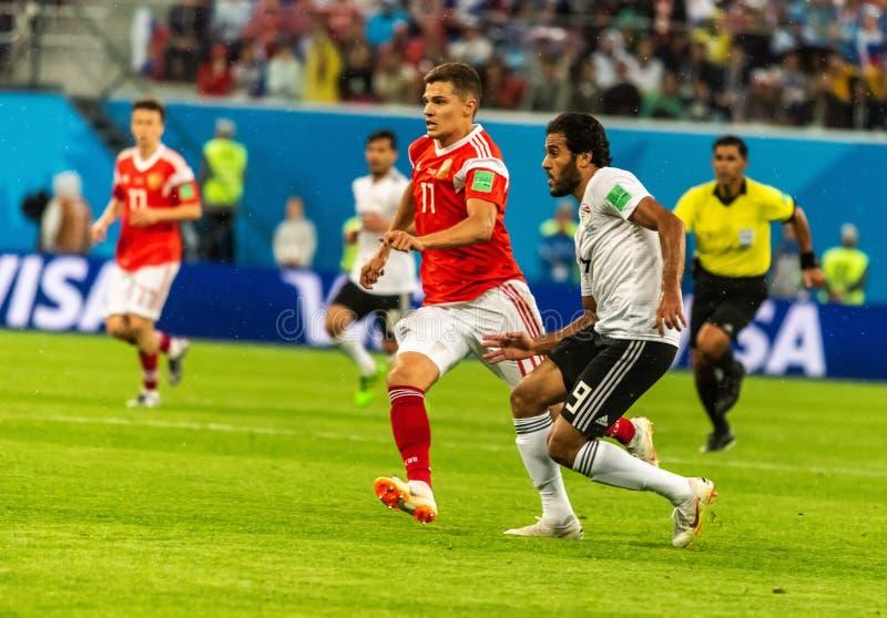 Egypt national team striker Marwan Mohsen against Russia national team midfielder Roman Zobnin. St Petersburg, Russia - June 19, 2018. Egypt national team royalty free stock image