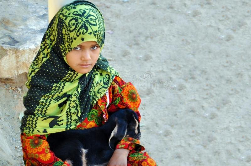 Egypt, October 22, 2012: A girl sits in a bright dress in a hijab with a baby goat in her arms royalty free stock photos