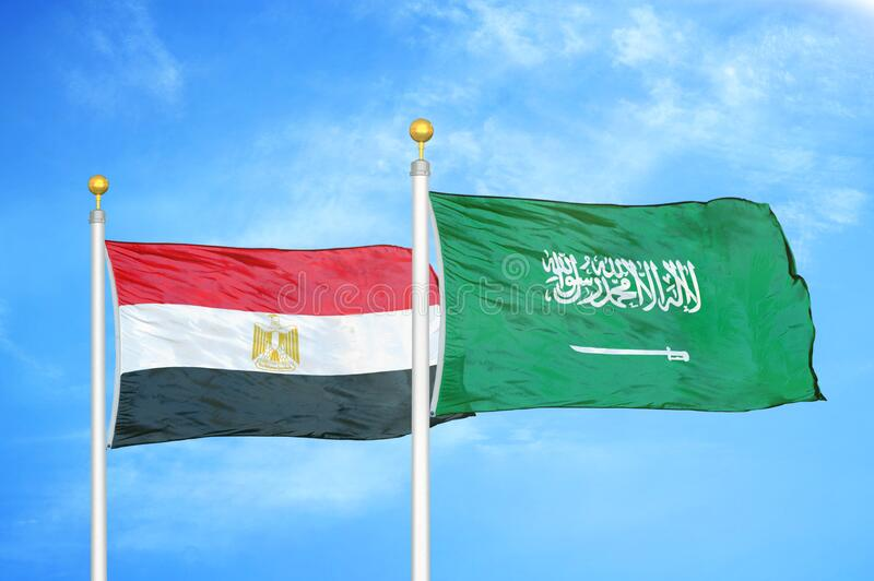 Egypt and Saudi Arabia two flags on flagpoles and blue cloudy sky. Background royalty free stock images