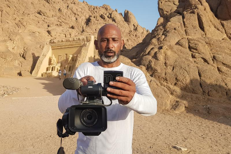 Egypt, Sharm El Sheikh - June 10, 2019: a black man in the desert shoots a video. professional landscape photographer. A stock image