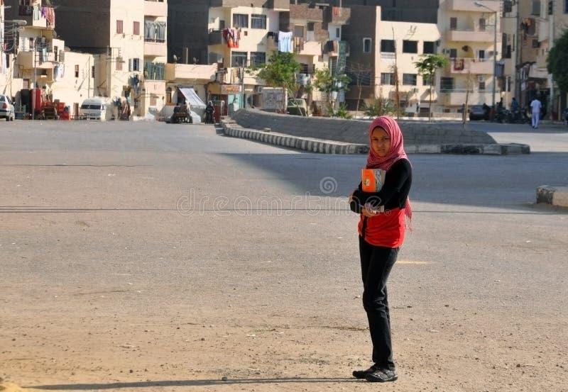 Egypte, 22 Oktober, 2012: Een schoolmeisjemeisje in een hijab met handboeken in haar handen bevindt zich op de straat royalty-vrije stock afbeelding